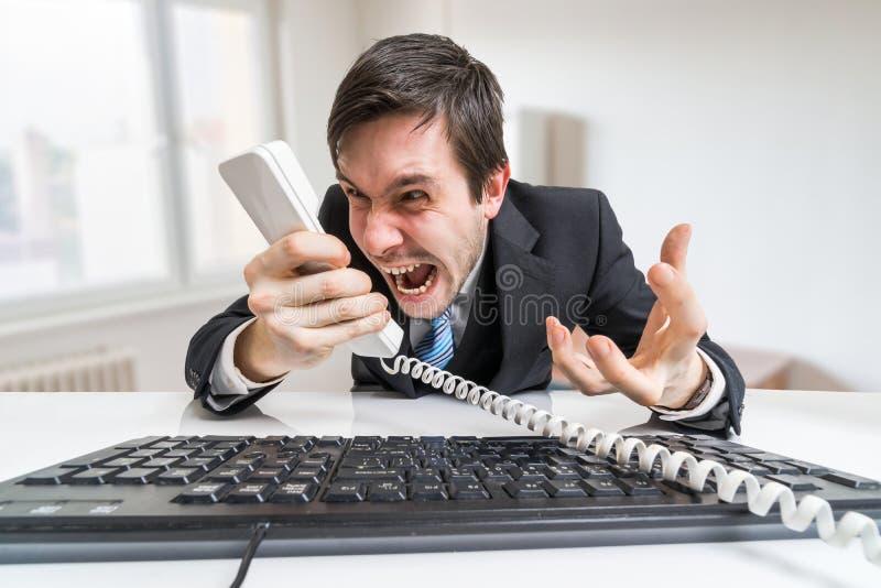 De boze werkgever of de manager roepen en schreeuwen aan de telefoon stock foto's