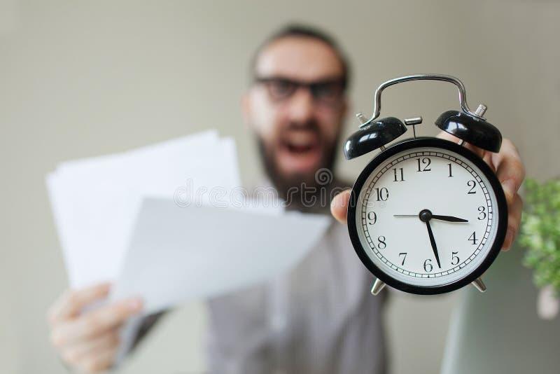 De boze werkgever met baard houdt wekker en documenten gillend stock foto