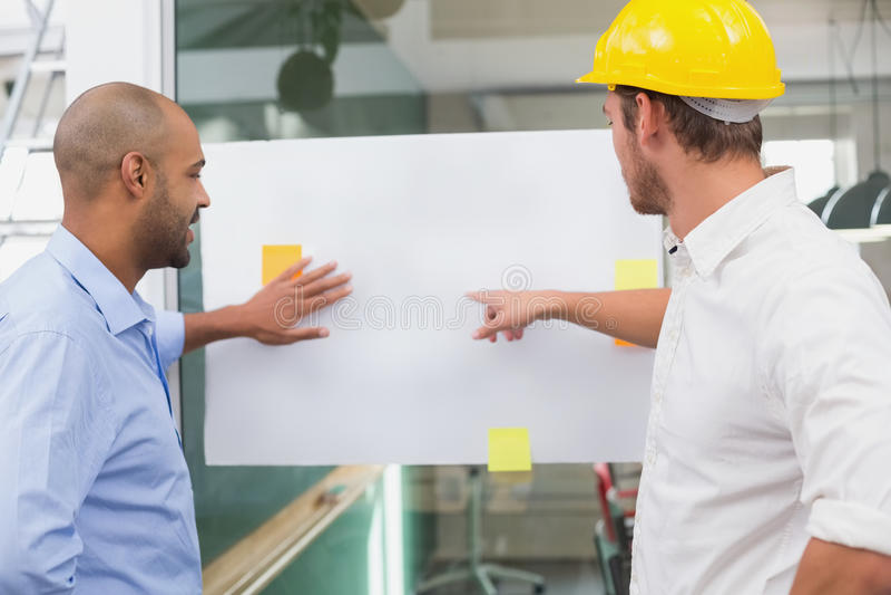 De brainstorming die van het architectenteam samen whiteboard bekijken stock afbeeldingen