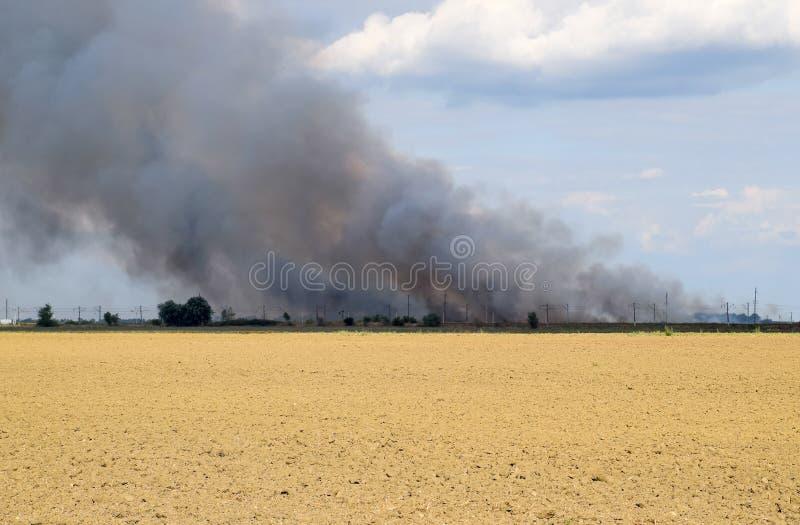 De brand is ergens voorbij het geploegde gebied Donkere rook van stock foto's