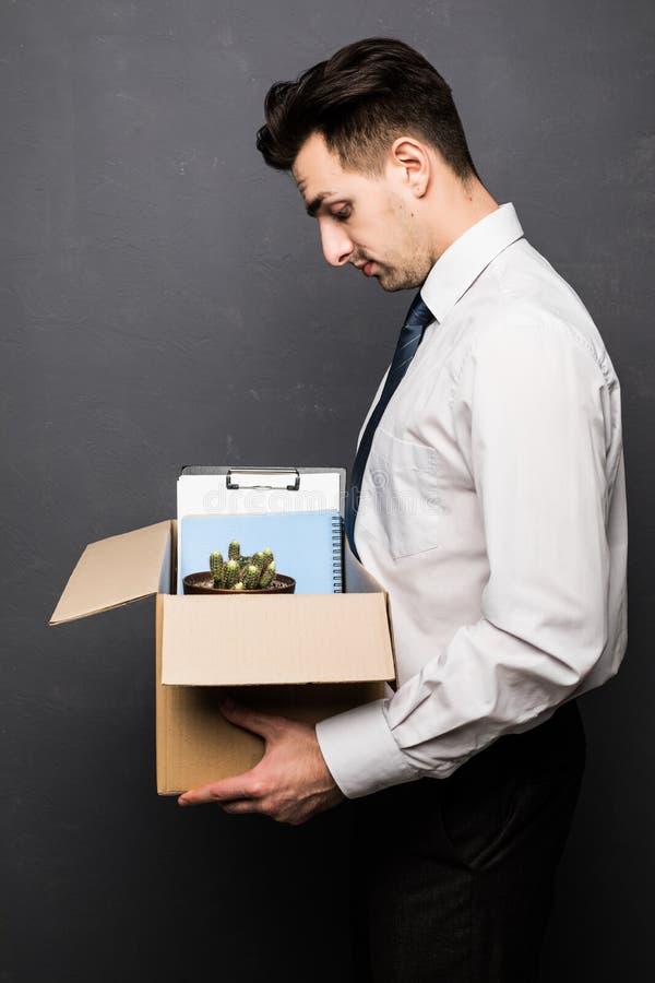 De in brand gestoken die doos van de zakenmanholding met persoonlijke bezittingen wordt op grijs in brand wordt gestoken stock afbeelding