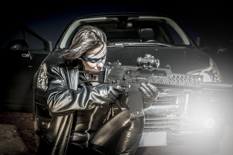 De brand, Gevaarlijke vrouw kleedde zich in zwart die latex, met kanon wordt bewapend. mede stock foto's