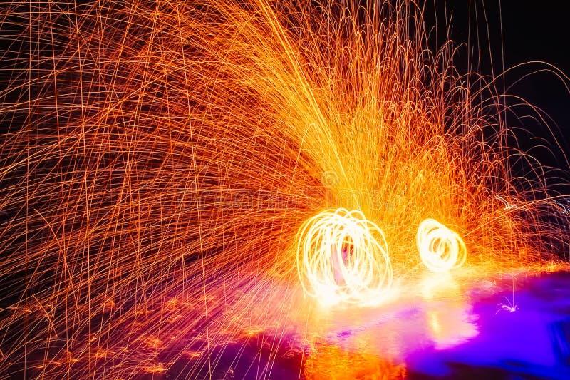 De brand toont Verbazende brandprestaties in de nacht Abstract Fife vonkt achtergrond De lang-blootstellingsfotografie vangt royalty-vrije stock foto