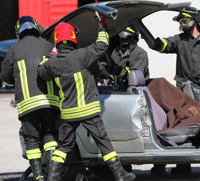 De brandbestrijders openen een schadeauto royalty-vrije stock foto's