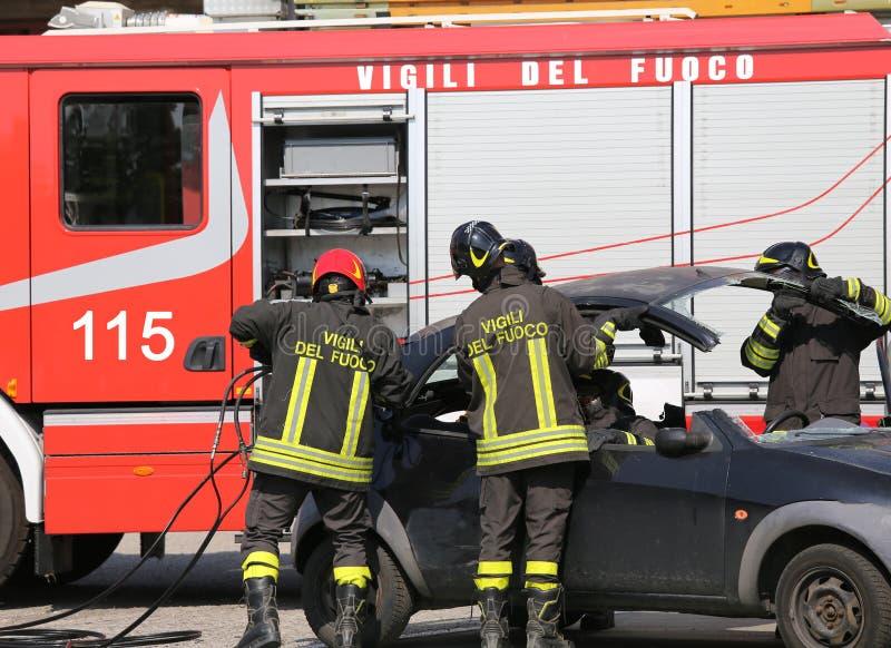 De brandbestrijders stijgen de kap van de auto na een autoongeval op stock afbeeldingen