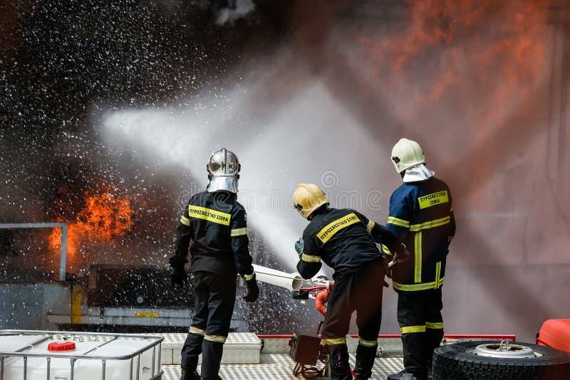 De brandbestrijders worstelen om de brand te doven die bij a uitbrak stock foto