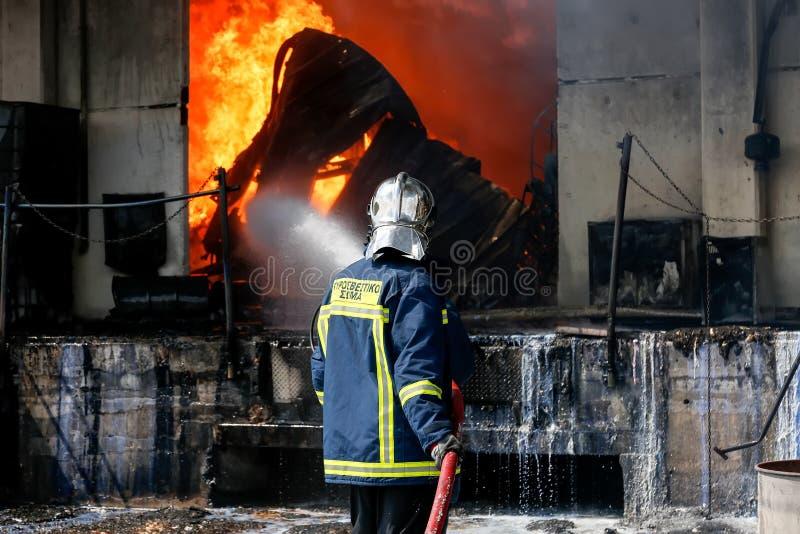 De brandbestrijders worstelen om de brand te doven die bij a uitbrak stock afbeeldingen
