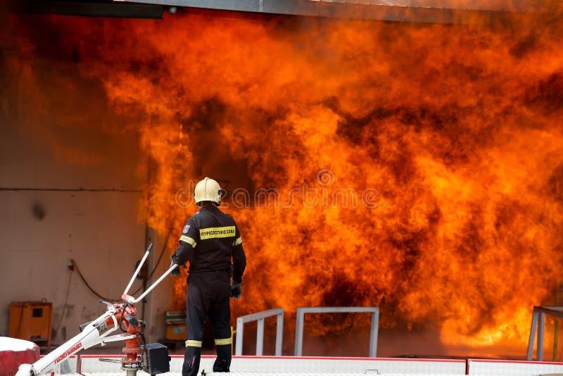 De brandbestrijders worstelen om de brand te doven die bij a uitbrak stock fotografie