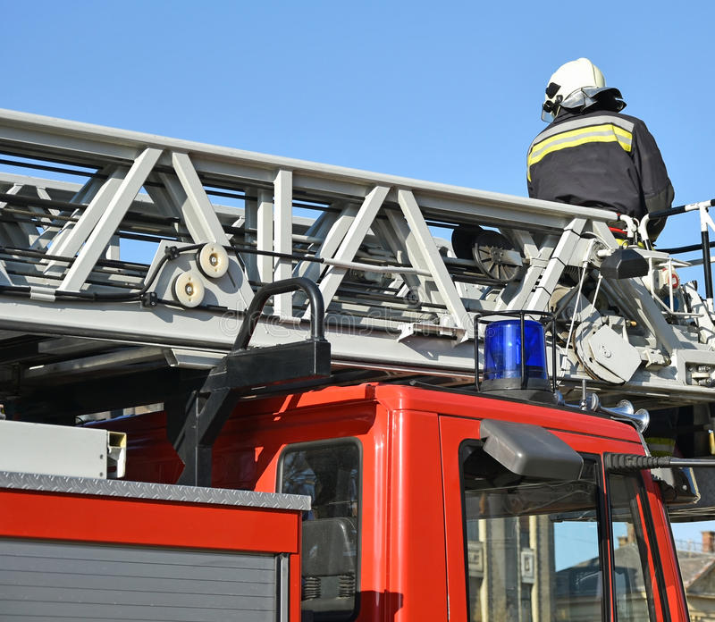 De brandbestrijderswerken aangaande de bovenkant van een brandvrachtwagen stock foto's