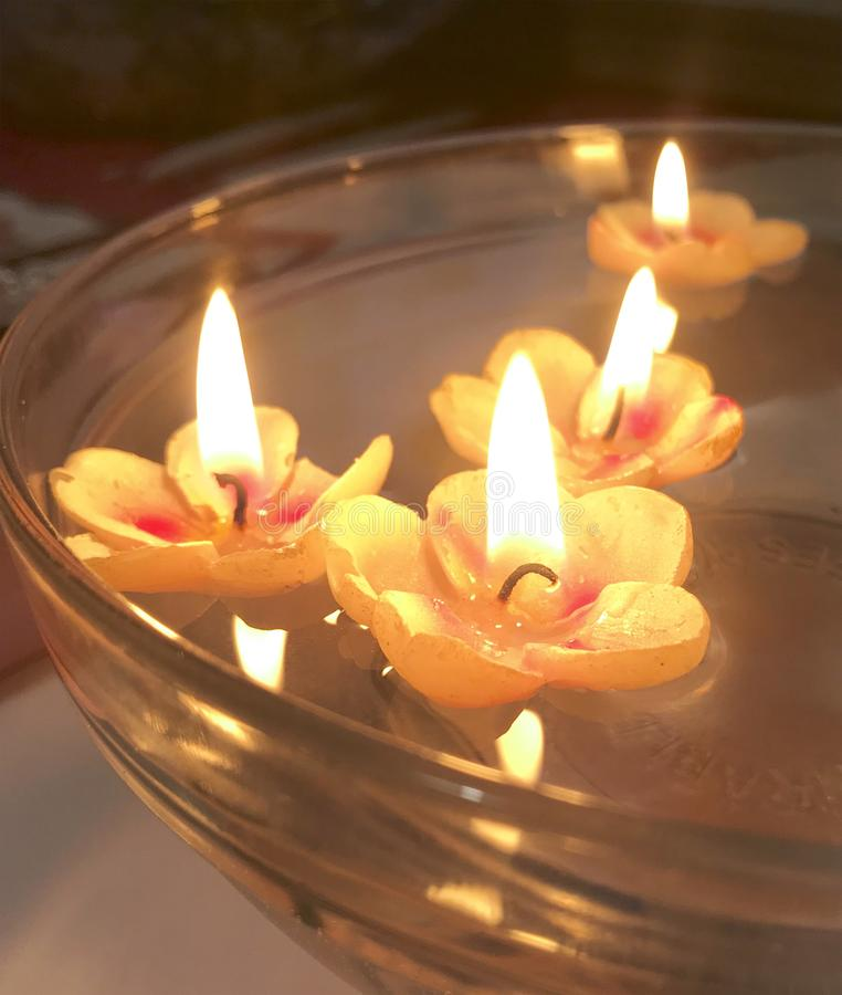 De brandende kaarsen in de vorm van bloemen drijven in het water royalty-vrije stock fotografie
