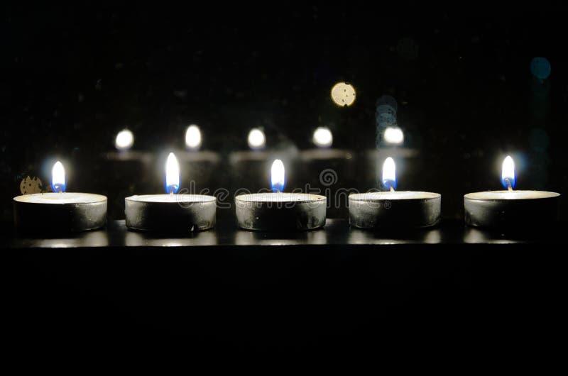 De brandende kleine kaarsen worden weerspiegeld in het venster waarachter de hoogteduisternis stock fotografie