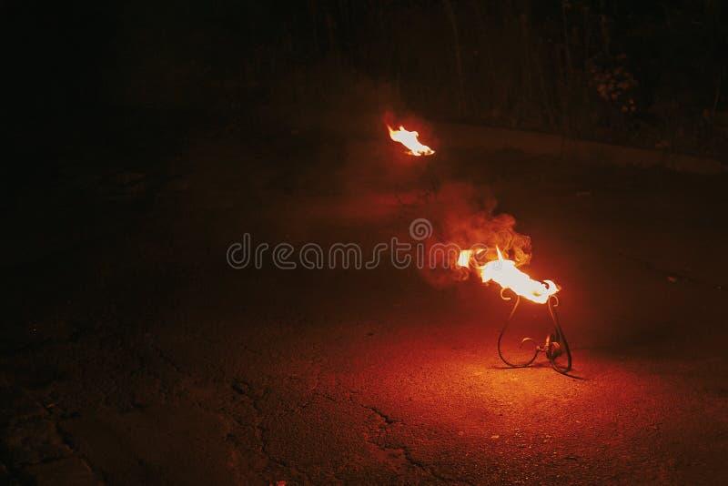 De brandende toorts met vlammen, verbazende brand toont bij nacht bij festiva stock foto's