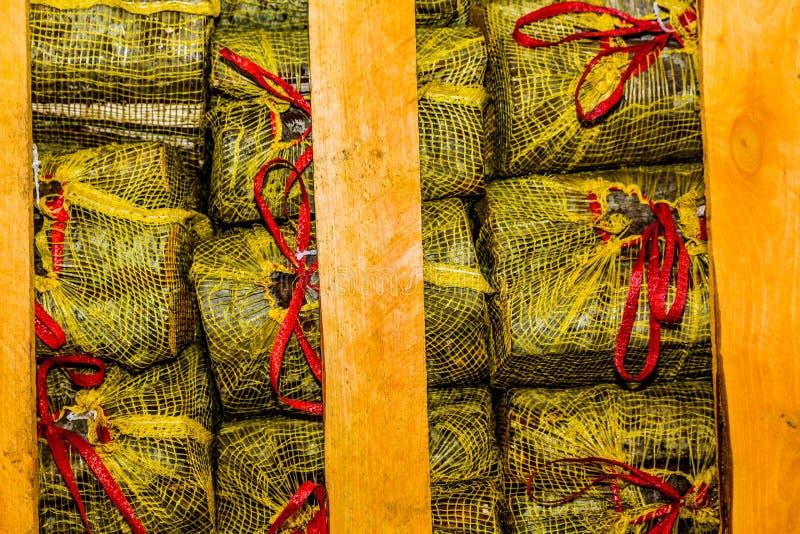 De brandhoutlogboeken sneden en plaatsten binnen gele zakken en bonden met een rood lint stock foto's