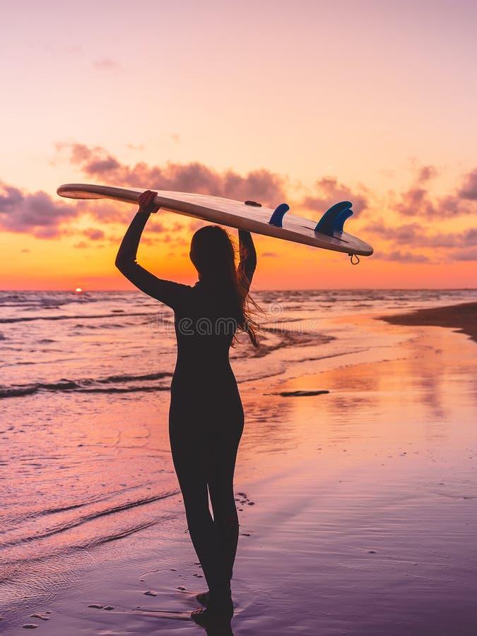 De brandingsvrouw gaat naar het surfen Meisje met surfplank op een strand bij zonsondergang of zonsopgang stock afbeelding
