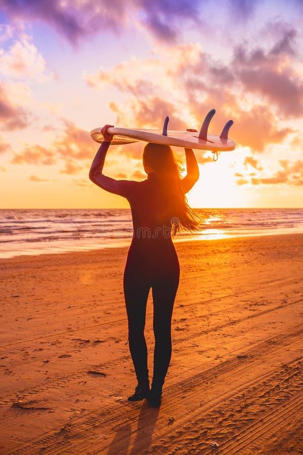 De brandingsvrouw met lang haar gaat naar het surfen Surfer met surfplank op een strand bij zonsondergang stock afbeelding