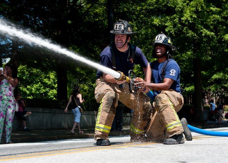 De brandweerlieden richten Slang op Doel in de de Verzamelingsconcurrentie van Atlanta stock afbeeldingen