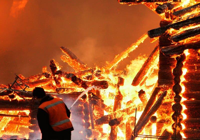 De brandweerman en de brand stock afbeeldingen