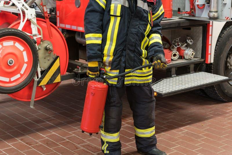 De brandweerman op de brandvrachtwagen gebruikte een brandblusapparaat stock afbeeldingen