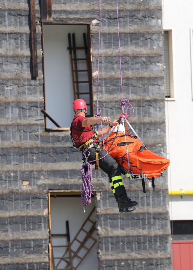 Download De Brandweerman Tijdens Een Oefening Draagt De Brancard Met Climbi Stock Afbeelding - Afbeelding bestaande uit afdeling, oefening: 54077095