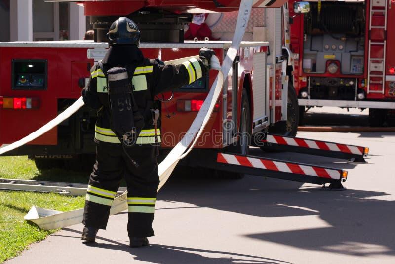 De brandweerman wikkelt de hydrant dichtbij de brandvrachtwagen af stock fotografie