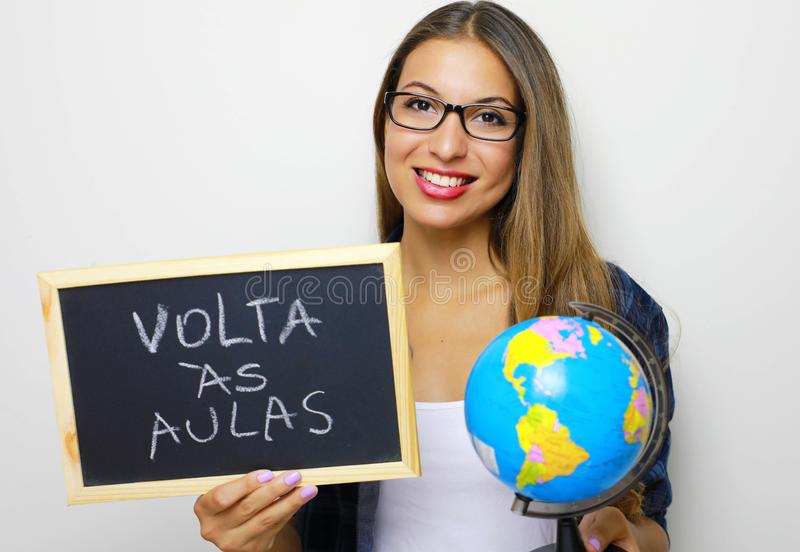 De Braziliaanse jonge vrouwelijke bol en het bord van de leraarsholding met Portugees geschreven 'Volta als aulas terug naar scho royalty-vrije stock foto's