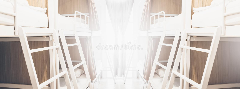 De brede slaapzaalbedden binnen de herbergenruimte voor toeristen of de studenten vertroebelden achtergrondbanner royalty-vrije stock foto's