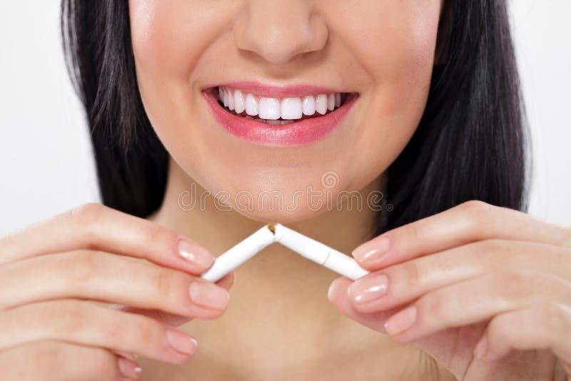 De brekende sigaret van de vrouw stock afbeelding
