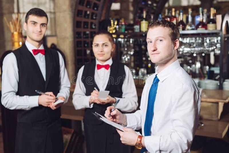 De briefing van de manager met de kelners Restaurantmanager en zijn personeel stock fotografie