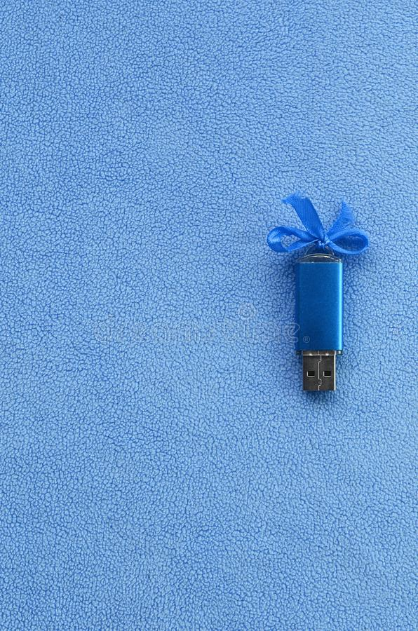 De briljante blauwe het geheugenkaart van de usbflits met een blauwe boog ligt op een deken van zachte en bont lichtblauwe vachts royalty-vrije stock fotografie