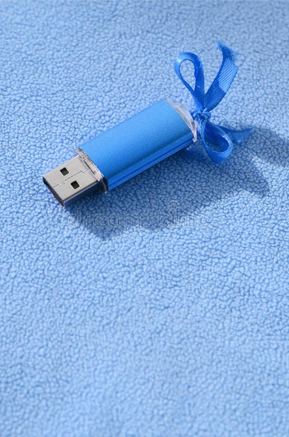 De briljante blauwe het geheugenkaart van de usbflits met een blauwe boog ligt op een deken van zachte en bont lichtblauwe vachts royalty-vrije stock afbeeldingen