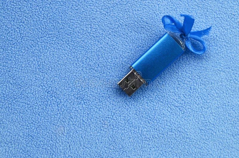 De briljante blauwe het geheugenkaart van de usbflits met een blauwe boog ligt op een deken van zachte en bont lichtblauwe vachts royalty-vrije stock afbeelding
