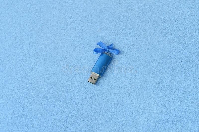 De briljante blauwe het geheugenkaart van de usbflits met een blauwe boog ligt op een deken van zachte en bont lichtblauwe vachts stock afbeeldingen