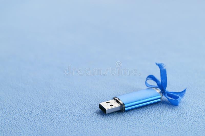De briljante blauwe het geheugenkaart van de usbflits met een blauwe boog ligt op een deken van zachte en bont lichtblauwe vachts stock afbeelding
