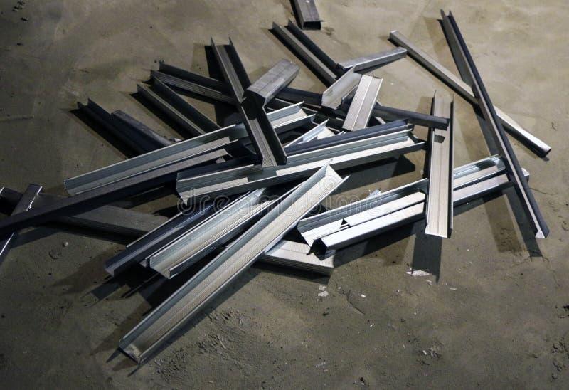 De briljante metaalprofielen voor het assembleren van skelet van isolatie ligt in stapel op beton stock afbeeldingen