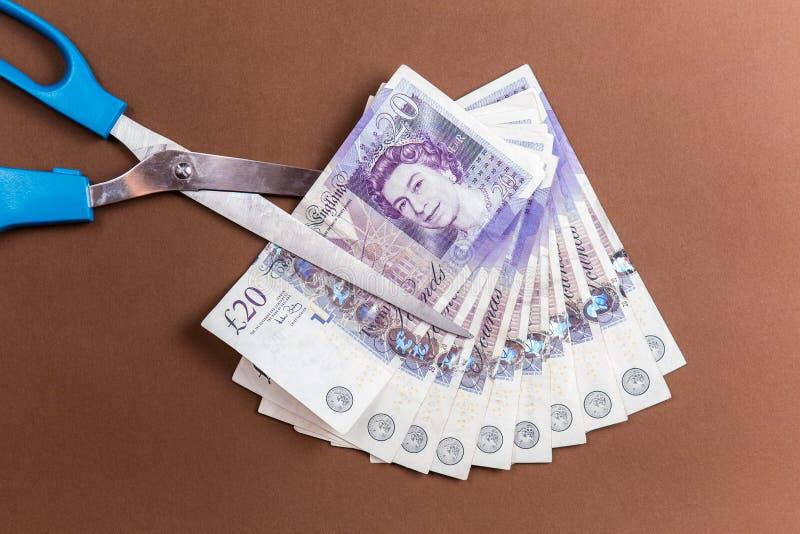De Britse geldachtergrond wordt 20 pondennota's gesneden door schaar stock foto
