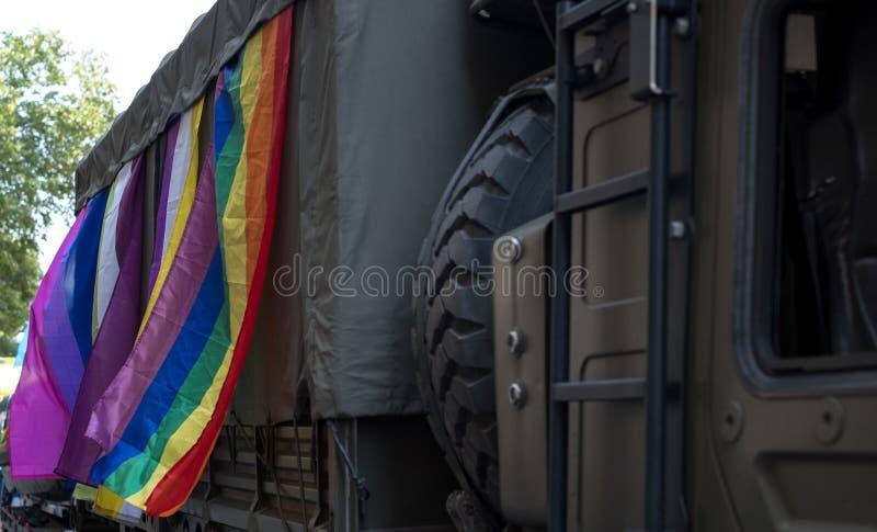De Britse militaire vrachtwagen neemt aan Vrolijk die Pride Parade deel, met regenboog en LGBT+-vlaggen wordt versierd royalty-vrije stock fotografie