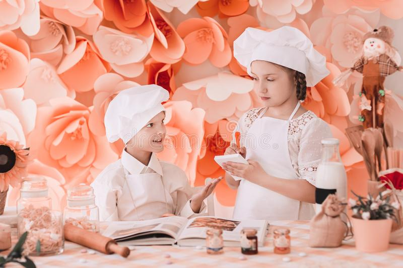 De broer en de zuster in eenvormige chef-koks registreren menu dat zich bij de keukenlijst bevindt royalty-vrije stock afbeeldingen