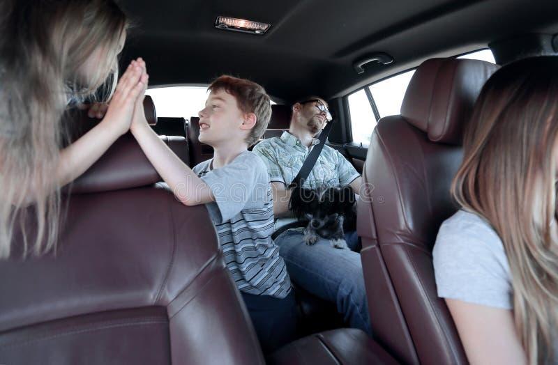 De broer en de zuster geven een hoogte vijf terwijl het zitten in de autocabine royalty-vrije stock foto