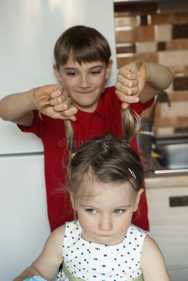 De broer en de zuster in de keuken en de jongen trekken het meisje door de staarten stock afbeelding