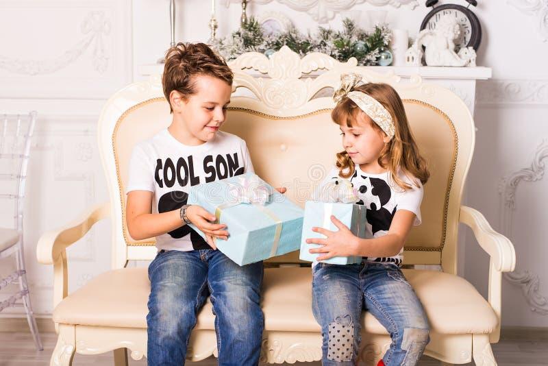 De broer gaat zijn zuster een gift voor Kerstmis of Nieuwjaar geven royalty-vrije stock afbeeldingen