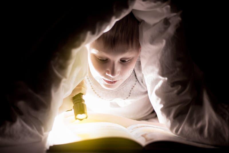 De broer leest een boek onder een deken met flitslicht Vrij jonge jongen die pret in kinderenruimte hebben royalty-vrije stock afbeelding