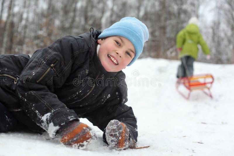 De broer ligt op sneeuw, trekt de zuster ar stock afbeeldingen