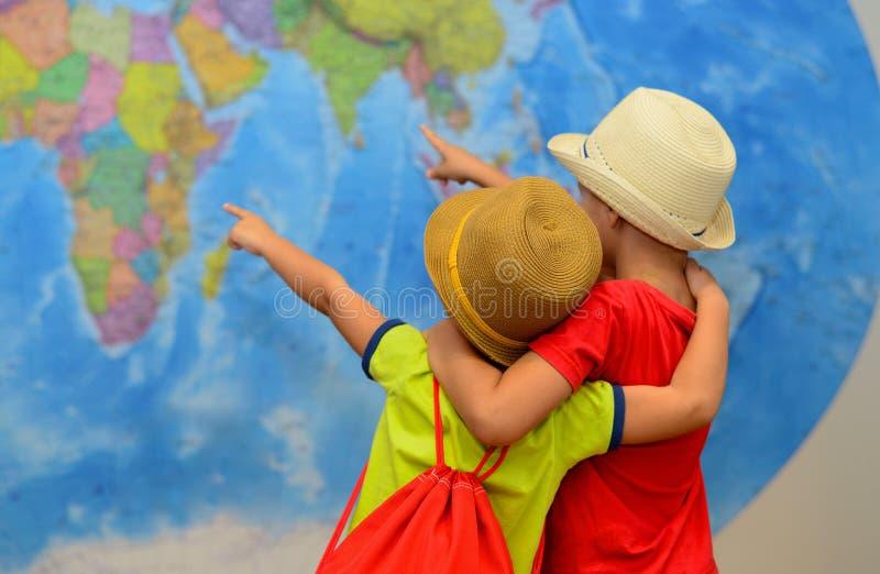 De broers speelt in reizigers Jongens voor een kaart van de wereld Avontuur en reisconcept Creatieve achtergrond royalty-vrije stock afbeeldingen