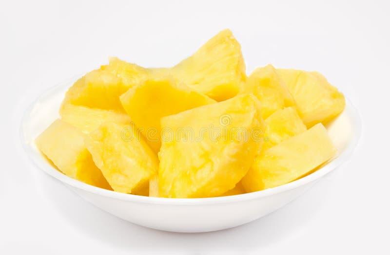 De brokken van de ananas in de geïsoleerde kom stock fotografie