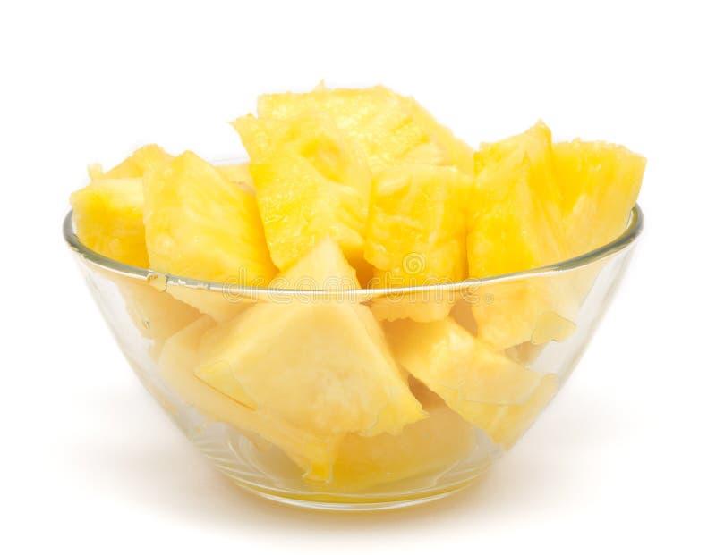 De brokken van de ananas in de geïsoleerdee kom stock foto's