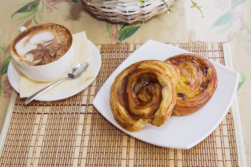 De broodjes en cappucino van de kaneelrookwolk stock afbeelding