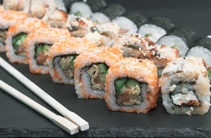 de broodjes van de sushireeks met van de de kaaskomkommer van de zalmpaling van de de rijstsaus de sesamkaviaar met eetstokjes stock afbeeldingen