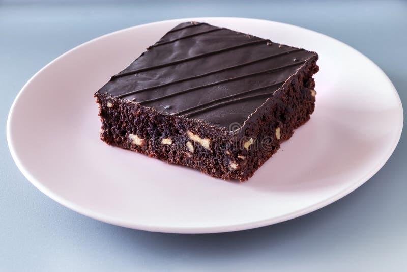 De browniecake van de chocoladeveganist met grijze achtergrond van de noten de roze plaat royalty-vrije stock afbeelding