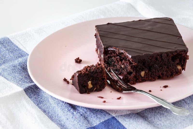 De browniecake van de chocoladeveganist met noten Roze plaat Lichte achtergrond stock fotografie