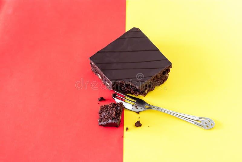 De browniecake van de chocoladeveganist met okkernoten Tweekleurige achtergrond Oranje en gele Hoogste menings In kleurrijke Sele stock afbeeldingen